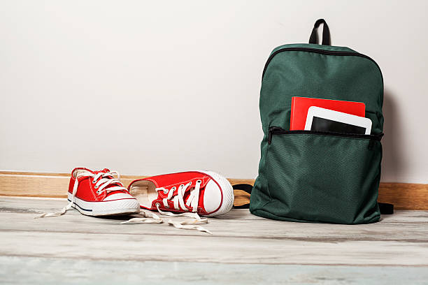 Red sneakers with school bag on wooden background stock photo