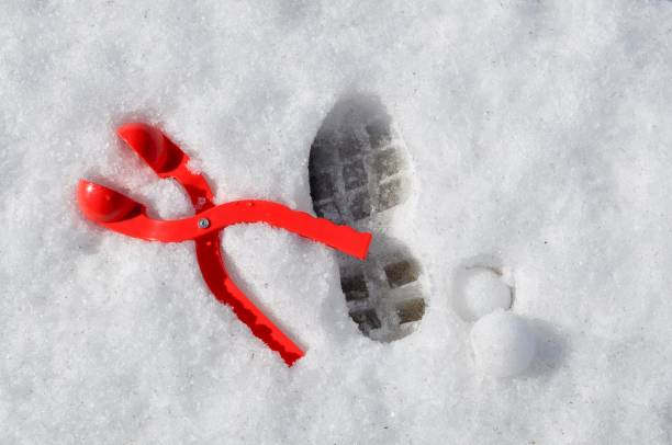 Red snow ball maker next to a foot print in the snow stock photo