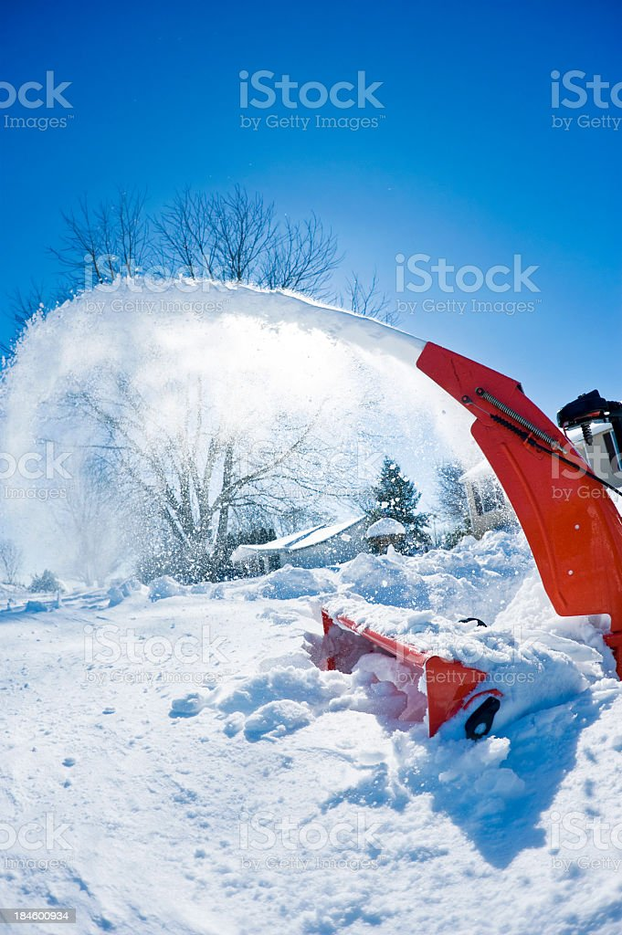 Red snowblower in deep snow blowing snow out back. stock photo