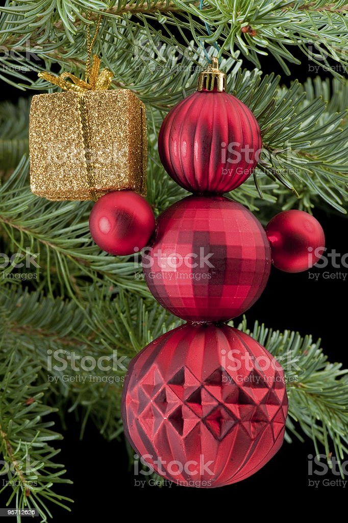 Red snowman holding golden gift box on pine branch royalty-free stock photo