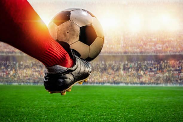 jugador de fútbol rojo pateando la acción del balón en el estadio - foto de stock