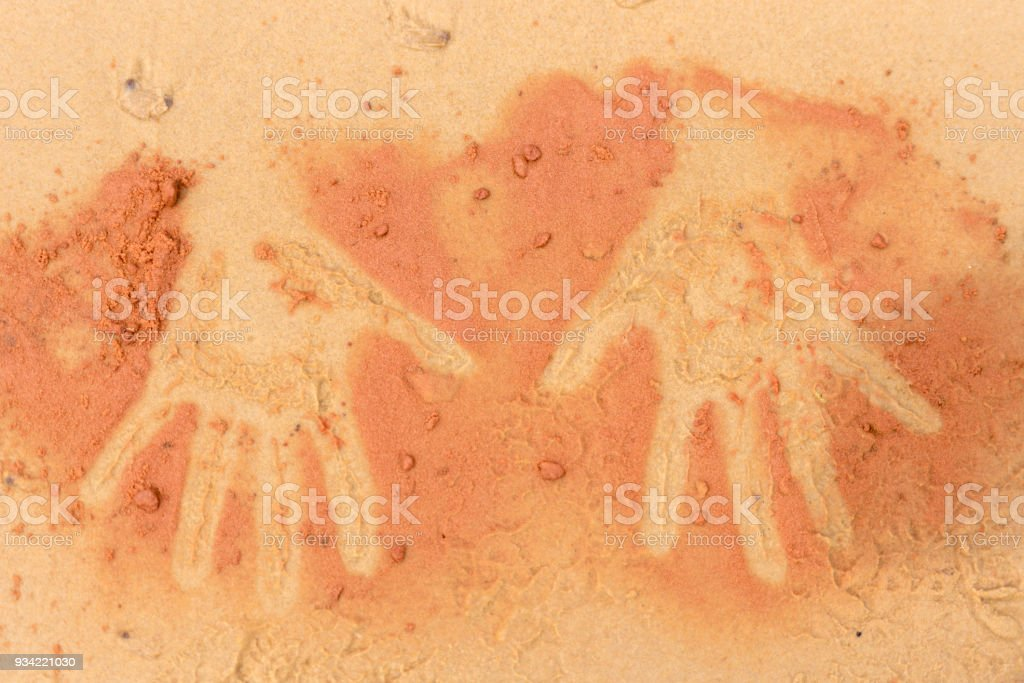 Red soil hand shape on sand in aboriginal art style stock photo