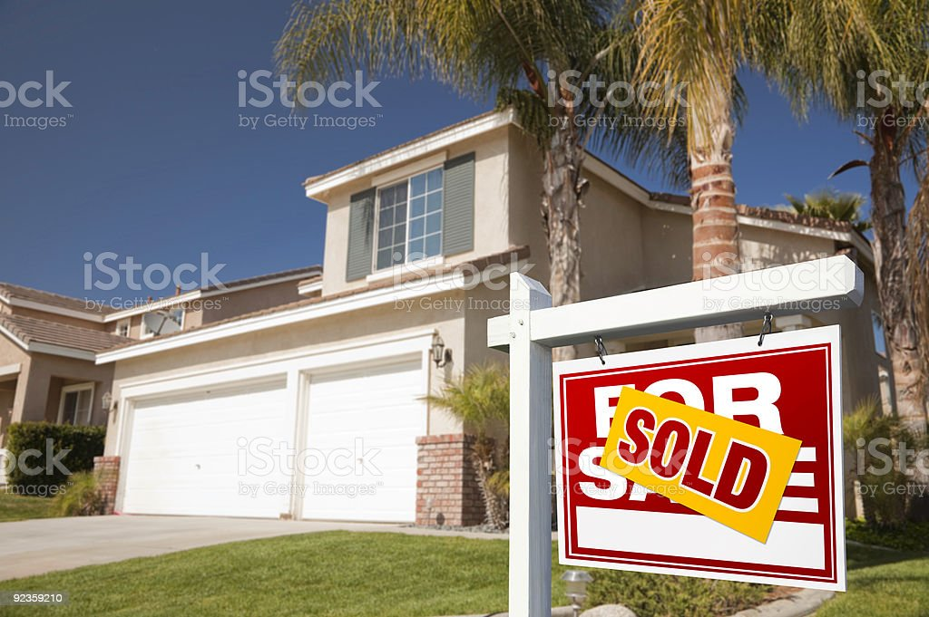 Red Sold For Sale Real Estate Sign and House stock photo