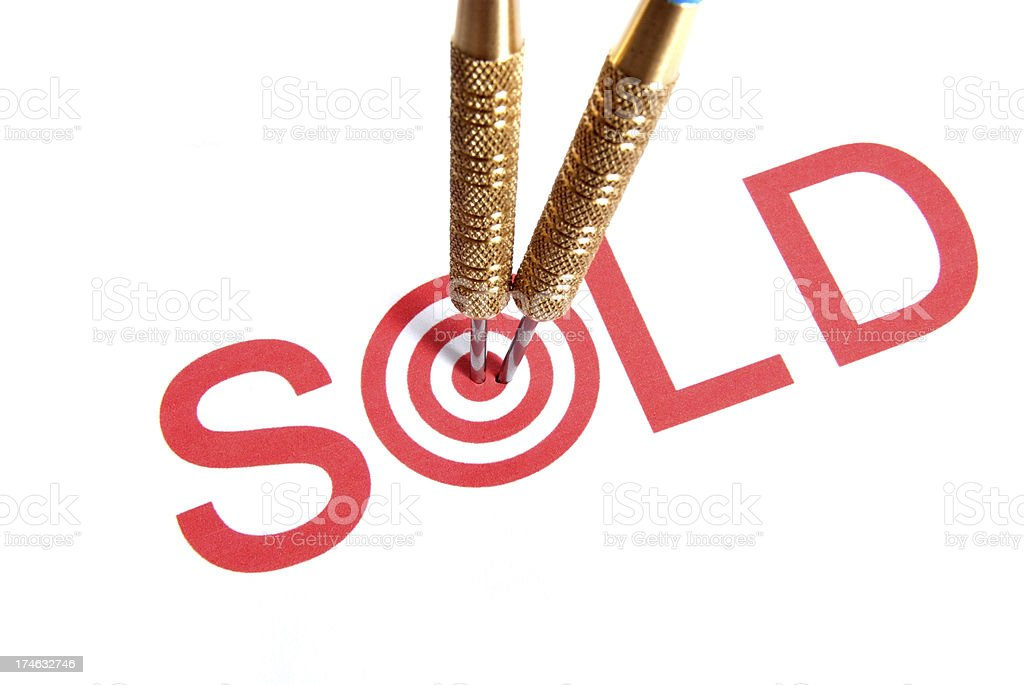 Red SOLD with bullseye for O with darts stuck in the O. royalty-free stock photo