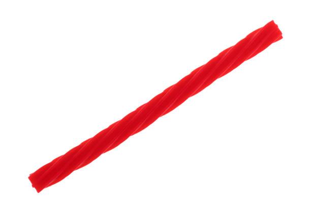 red spiral licorice stick on a white background - liquirizia foto e immagini stock