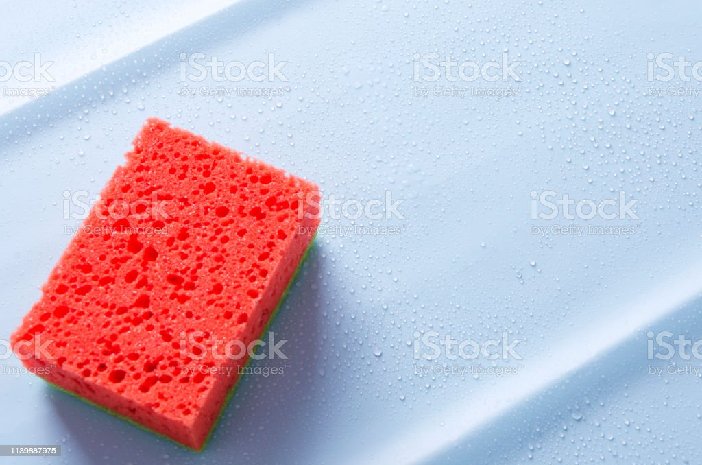 Closeup of kitchen scrub brush against blue surface and water drops...
