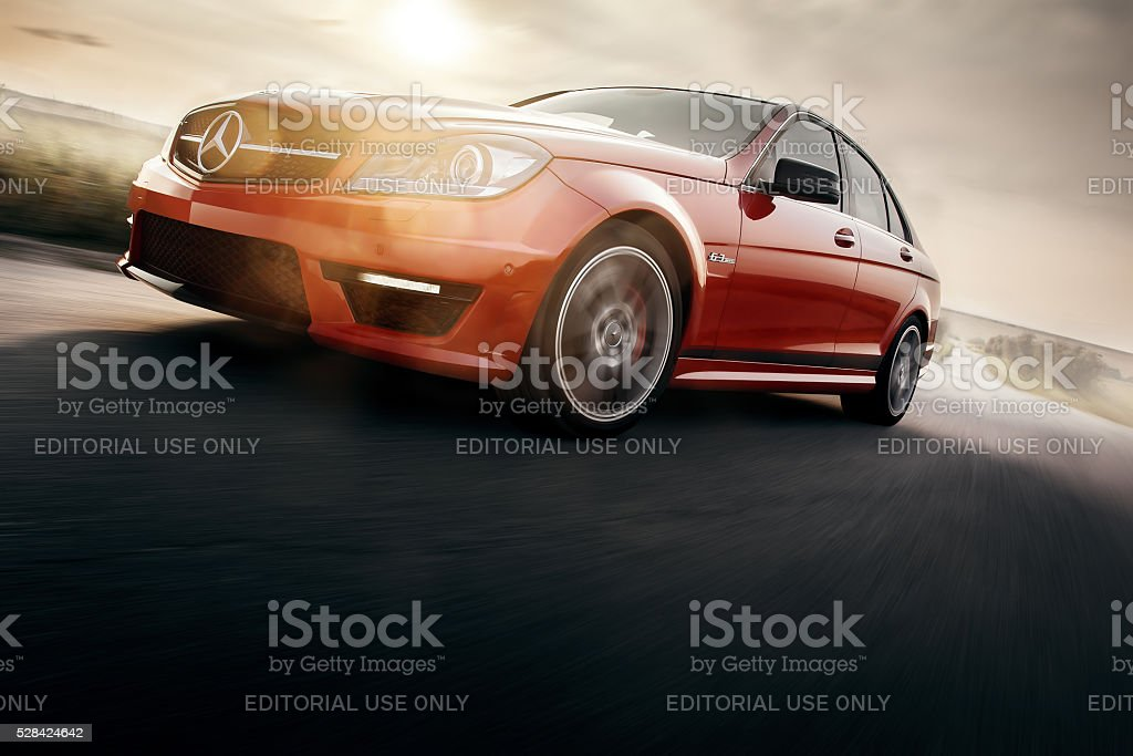 Red Sport Car Drive Speed On Asphalt Road At Sunset Saratov, Russia - August 24, 2014: Mercedes-Benz C63 AMG car drive on road at sunset Asphalt Stock Photo