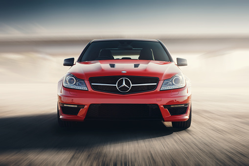 Red Sport Car Drive Speed On Asphalt Road At Sunset Stock Photo - Download Image Now