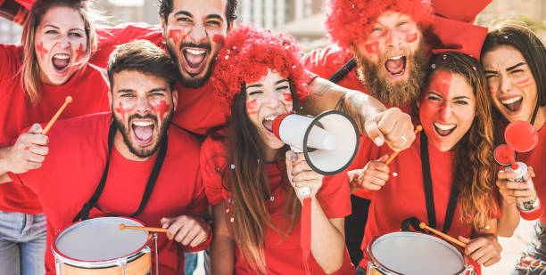 Red sport fans screaming while supporting their team out of the stadium - Football supporters having fun at competion event - Champions and winning concept - Focus on center girl face stock photo