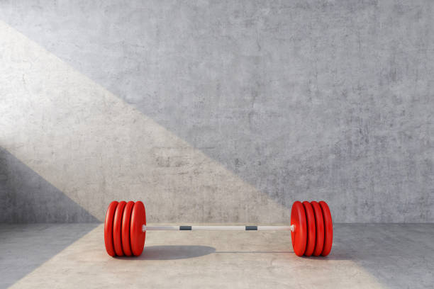 red sports barbell on the background of a concrete wall stock photo