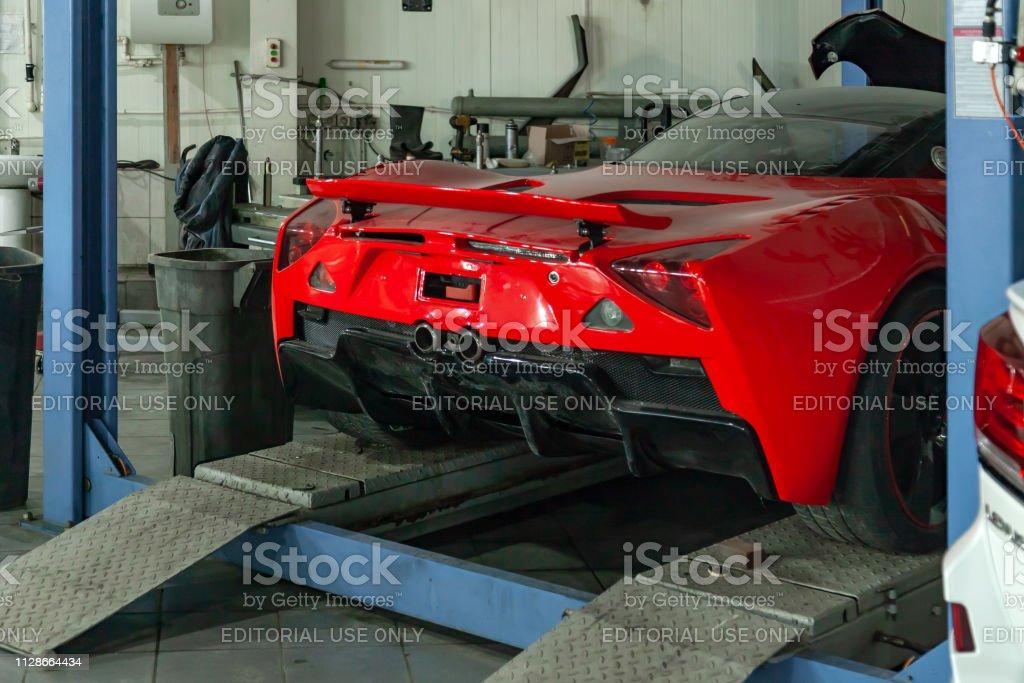 Coche deportivo rojo levantado en un elevador de un taller de reparación de automóviles, parachoques trasero y alerón - foto de stock