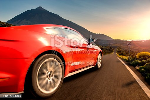 Red sports car running at high speed on the way .Ford Mustang,road in Tenerife