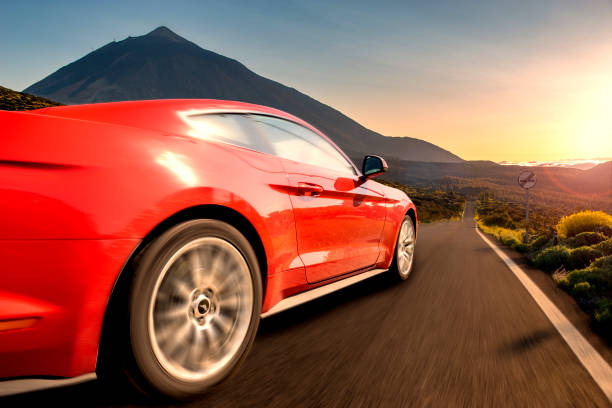 Red sports car running at high speed on the way .Ford Mustang,road in Tenerife Red sports car running at high speed on the way .Ford Mustang,road in Tenerife red car stock pictures, royalty-free photos & images