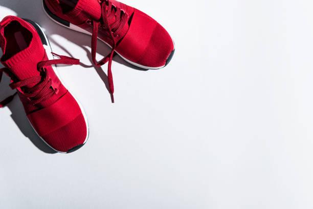 rote sportschuhe isoliert auf grau - joggingschuhe stock-fotos und bilder
