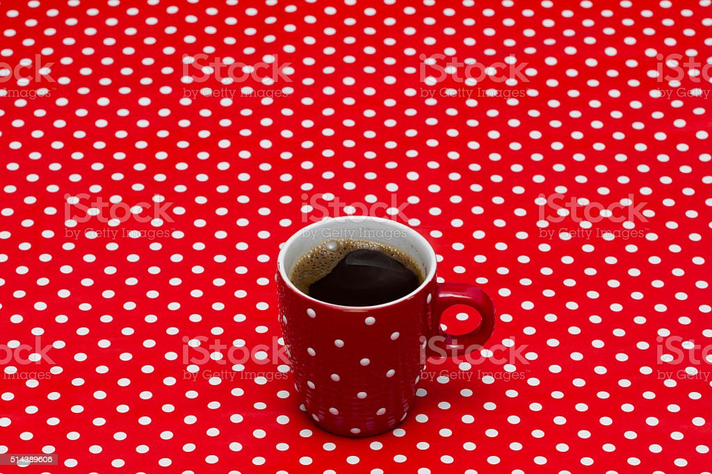 Red spotted cup of black coffee on red spotted tablecloth stock photo