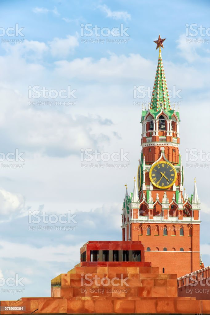 Red square, Moscow, Russia. Spasskaya tower of Kremlin with star and clock and Lenin's Mausoleum. Vertical composition, copy space on the cloudy sky. stock photo