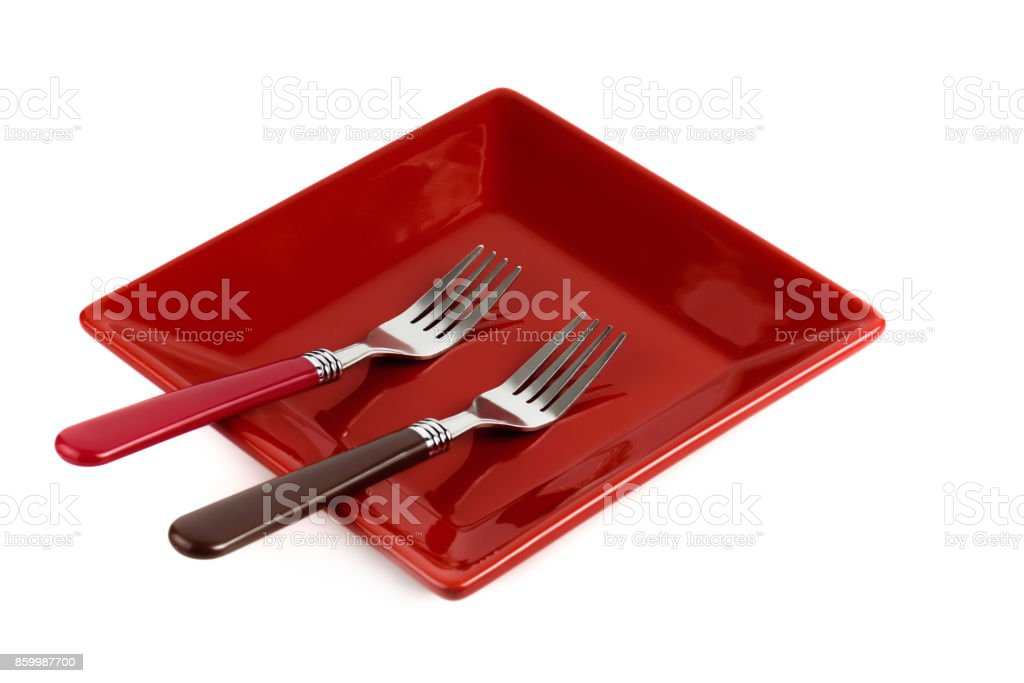 Red square plate and two forks on a white background. stock photo