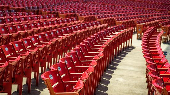 Red stadium chairs in an empty stadium.