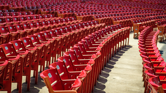 Red stadium chairs in an empty stadium.