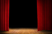 close up red stage curtain opening over wooden floor stage