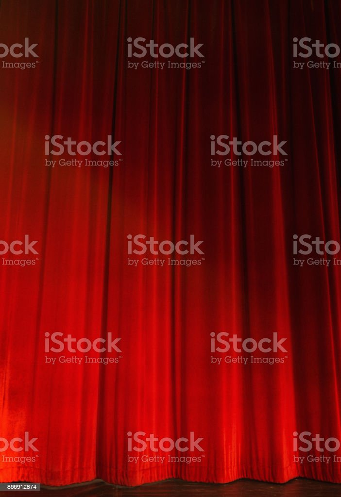 Red stage curtains, closed, lit by footlights stock photo