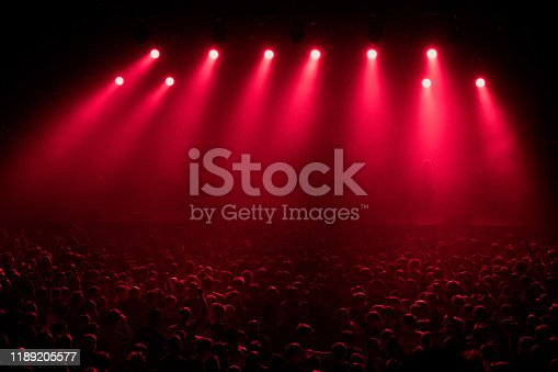 red concert light equipment and crowd of unrecognized people at big music concert in nightclub