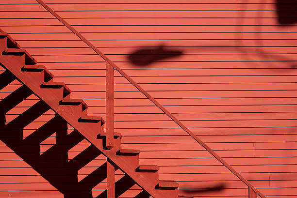 Red staircase on the red barn with shadows stock photo