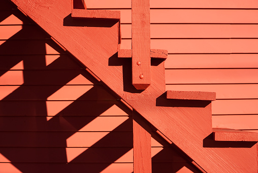 Close up on red stairs of the red building with shadows from the sun