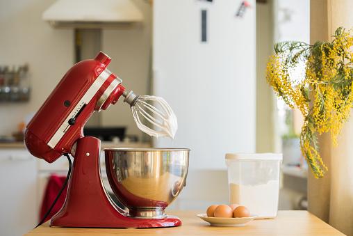 red stand mixer mixing white cream, kitchen