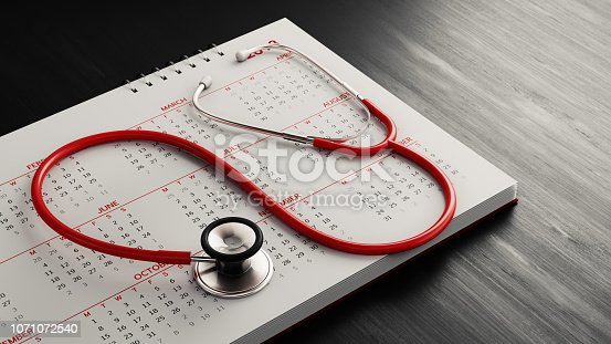 Red stethoscope and a calendar on black wood surface. Horizontal composition with copy space. Health and reminder concept with selective focus.