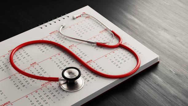 stéthoscope rouge ainsi qu'un calendrier sur la surface du bois noir - calendrier digital journée photos et images de collection