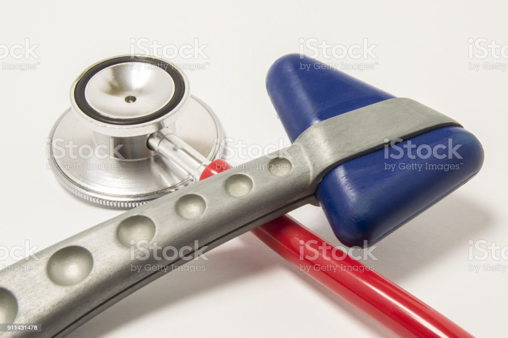 Red stethoscope and neurological reflex hammer with blue triangular head lie crosswise on white background on doctor workplace. Equipment for physical examination in neurology and internal medicine stock photo