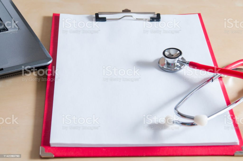 Red stethoscope on a red clipboard. Near laptop. Medical device....