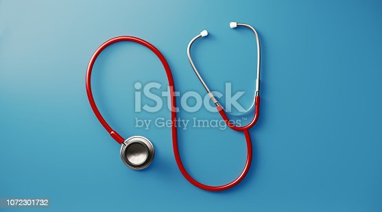 Red stethoscope on blue background. Health concept. Horizontal composition with copy space. Directly above.