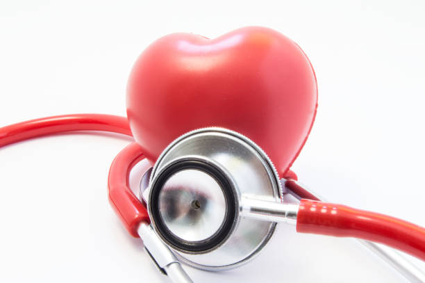 red stethoscope or phonendoscope with chrome chestpiece carries out survey of heart figure front view. concept for protection, treatment and prevention of heart from diseases of cardiovascular system - defection stock photos and pictures