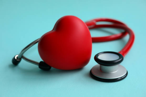 Red stethoscope with heart on blue modern background stock photo