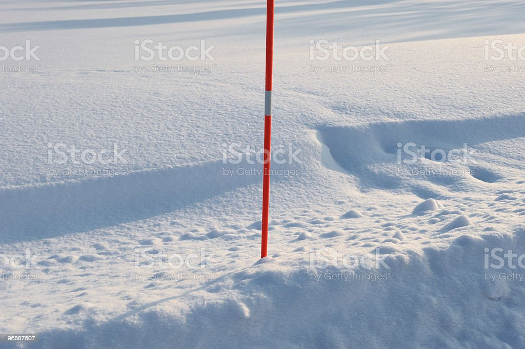 Red stick in the snow stock photo