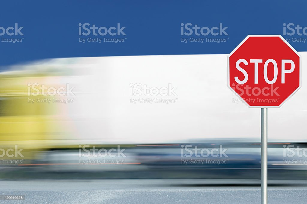 Red stop road sign, motion blurred truck vehicle traffic background stock photo