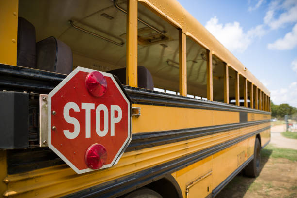 a red stop sign with lights on the side of an old yellow school bus. back to school - school buses stock pictures, royalty-free photos & images