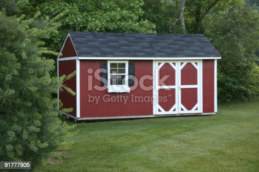 Red & white storage or potting shed set in a suburban setting surrounded by trees.