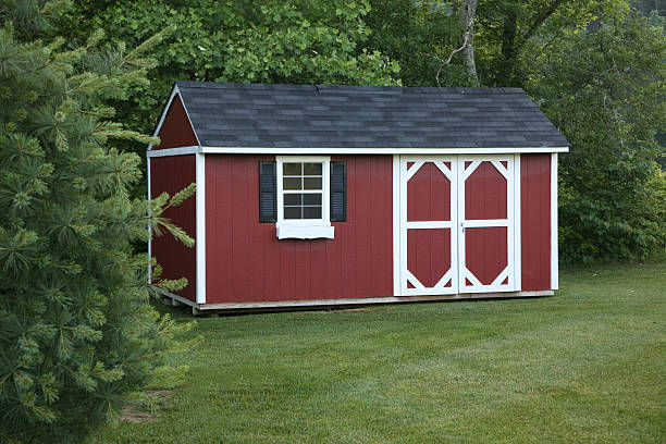 A red storage shed in the lawn stock photo