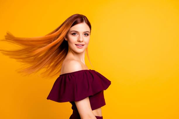 roten geraden haaren attraktive süßes schönes fröhliches junges mädchen, hälfte gedreht, wind wehenden haare. über hell lebhaft gelbe hintergrund isoliert - rotes oberteil stock-fotos und bilder
