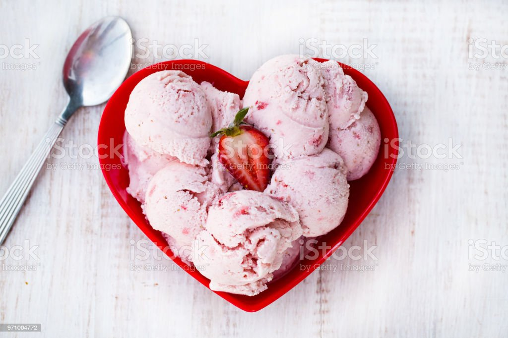 Red Strawberry Ice Cream In Heart Shaped Bowl stock photo