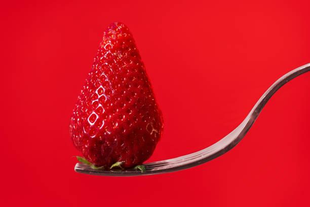 Rote Erdbeere auf Gabel mit rotem Display-Hintergrund – Foto