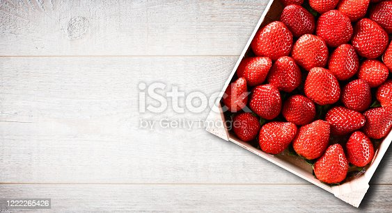 Strawberries in wood box white line table. Fresh forest strawberry top view. Copy space for text.