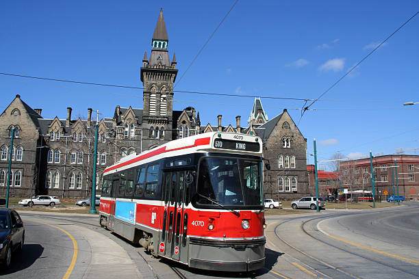 a red street tram in toronto, canada - toronto streetcar stock photos and pictures