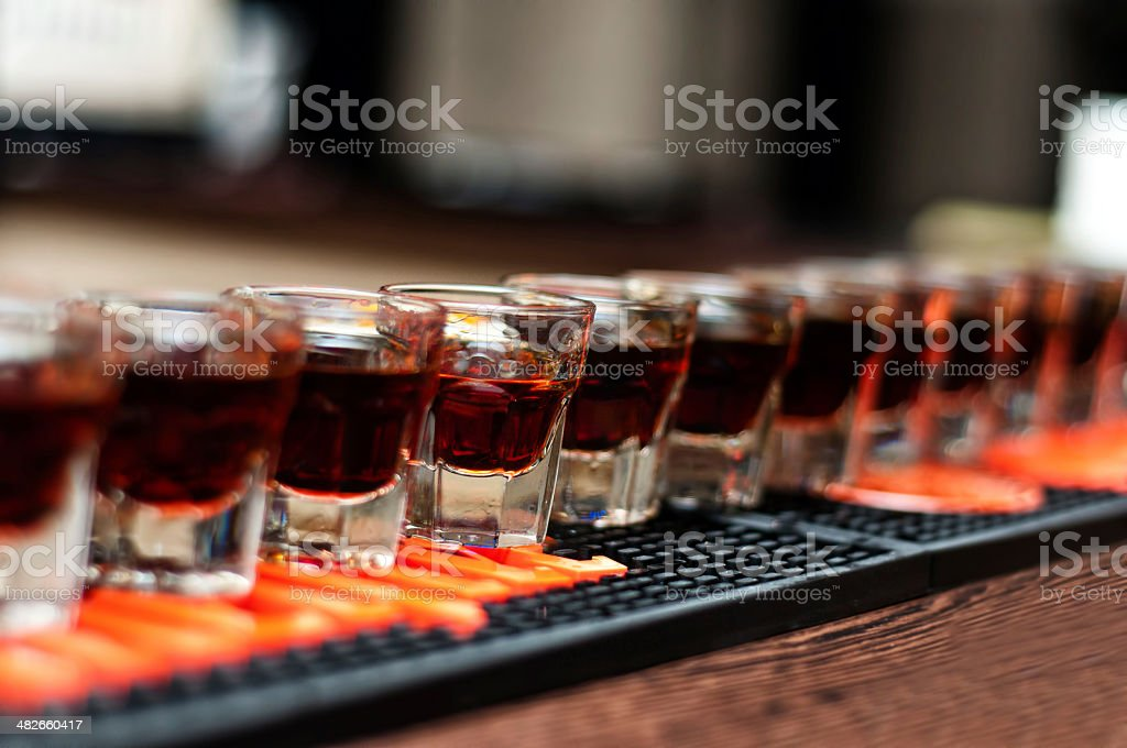 Red, strong alcoholic drink in small glasses on bar royalty-free stock photo