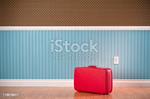 Red vinyl suitcase in empty room. The wall has a blue beadboard wainscoting and a patterned wallpaper.*