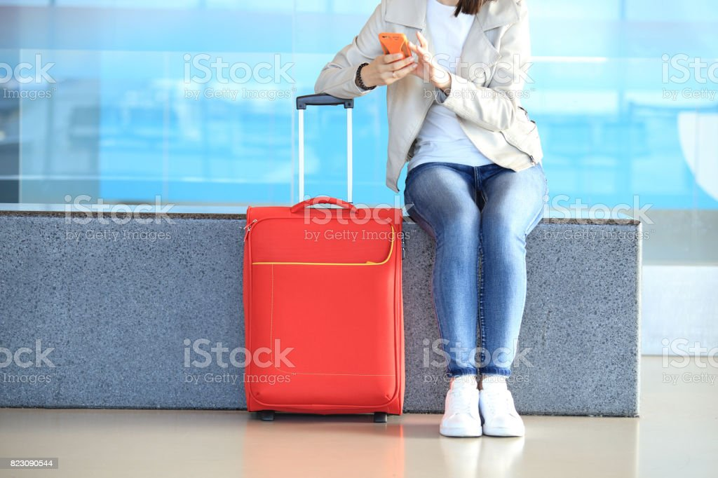 Red suitcase near sitting girl stock photo