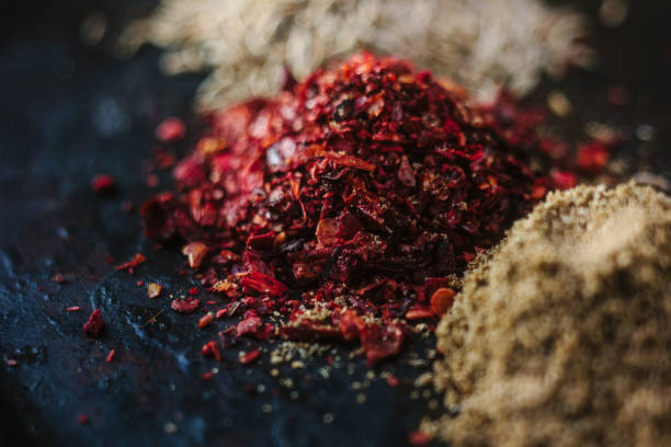Red sumac spice on black metal plate surrounded by other spices. stock photo